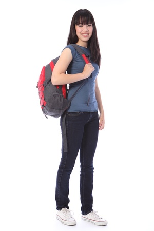 Beautiful smiling young Japanese teenager high school student girl wearing blue denim jeans and t-shirt, school backpack over shoulder.