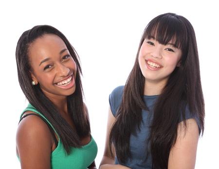 laughing out loud: Riendo en voz alta son dos amigos felices hermosas adolescentes, una mezcla de raza afroamericana y orientales chicas japonesas con una gran sonrisa y el pelo largo y negro.