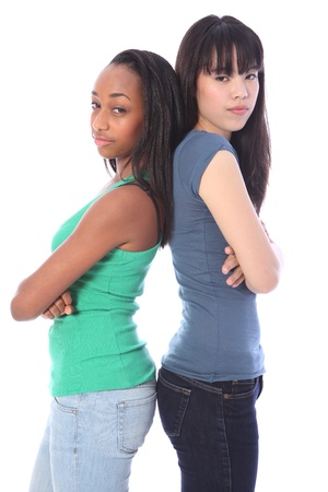high school girl: Two pretty teenage friends, a mixed race african american and oriental Japanese girls standing back to back with playful serious mean scowling expressions.  Stock Photo