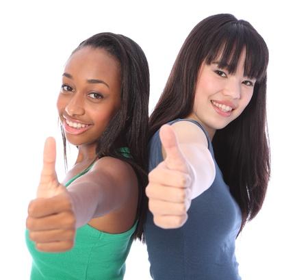 Dos amigos adolescentes hermosas, una mezcla de raza afroamericana y orientales chicas japonesas de pie espalda con espalda dando pulgares positivos del inicio de sesi�n con grandes sonrisas felices.