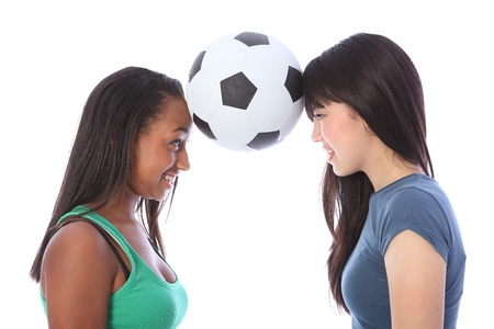 Two beautiful teenage friends, a mixed race african american and oriental Japanese girls having fun balancing soccer ball between their foreheads. Zdjęcie Seryjne