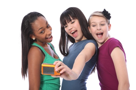 three friends: Fun photography with digital camera for three pretty young teenager girl friends a blonde caucasian, an oriental Japanese and an African American mixed race student all having a laugh together.