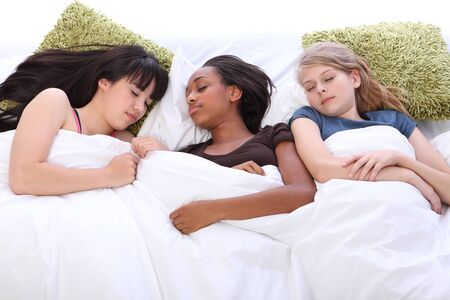 sleepover: Falling asleep at slumber party for three tired beautiful teenage girl friends, a mixed race african american, oriental Japanese and blonde caucasian school mates.