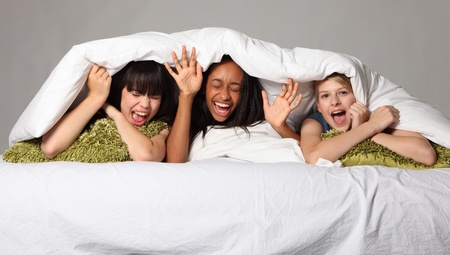 sleepover: Hilarious fun and scream with laughter at sleepover party for three happy beautiful teenage girl friends, a mixed race african american, oriental Japanese and blonde caucasian school mates.