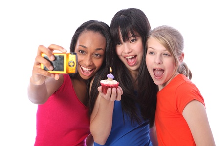 Birthday celebration photograph with candle on cakes for three beautiful young teenager girl friends a blonde caucasian, an oriental Japanese and an African American girl holding the camera. Stock Photo - 11025266