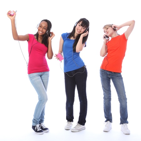woman black background: Three beautiful young teenager girl friends a blonde caucasian, an oriental Japanese and an African American girl having fun listening to cell phone music and dancing.