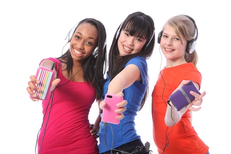 Three beautiful young teenager girl friends a blonde caucasian, an oriental Japanese and an African American girl having fun listening to cell phone music on headphones.