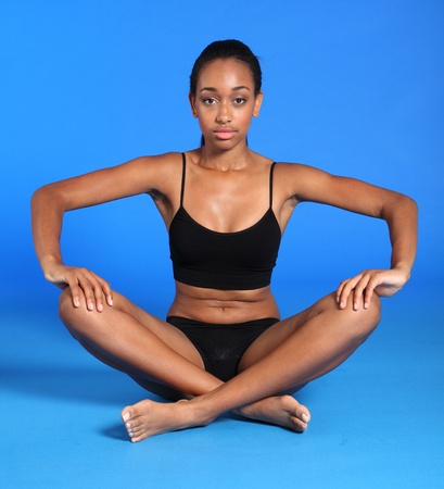 Beautiful athletic african american sportswoman wearing black vest and briefs underwear, sitting cross legged against blue background showing off fit and healthy body. photo