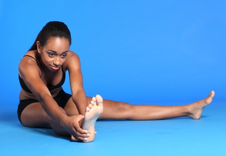 Beautiful young athletic african american sportswoman wearing black sports vest and briefs underwear, sitting on floor barefoot doing hamstring stretch exercise. photo