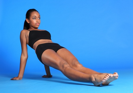 Body and torso stretch exercise by beautiful young athletic african american fitness woman wearing black sports bra and briefs underwear. photo