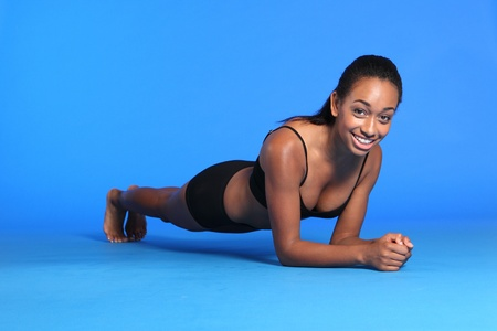 Stomach muscle building with the plank ab exercise lying on floor by a beautiful young athletic african american fitness woman wearing black sports bra and briefs underwear. photo