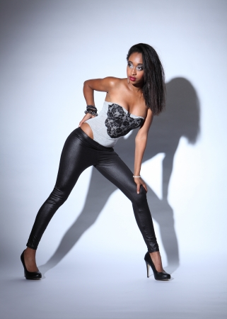 Sexy young african american fashion model wearing grey body suit with black shiny leggings and stiletto heels, wearing silver and white make up. photo