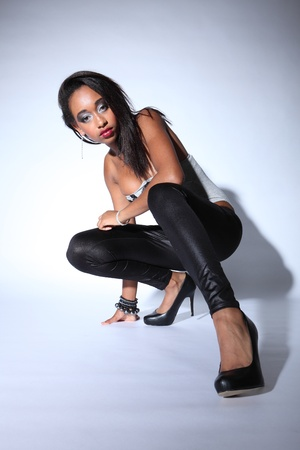 Sexy kneeling pose with attitude by young african american fashion model wearing grey body suit with black shiny leggings and stiletto heels, wearing silver and white make up. photo