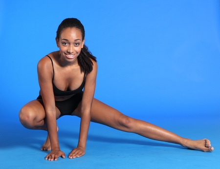 Crouching leg stretch exercise on floor by a beautiful young athletic african american fitness woman wearing black sports bra and briefs underwear. photo