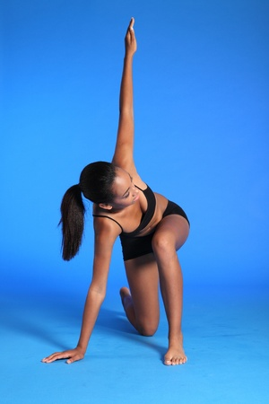 Fitness warm up stretch exercise on floor by a beautiful young athletic african american fitness woman wearing black sports bra and briefs underwear. photo