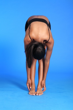 bending over: Fitness warm up stretch exercise bending over touching toes by a beautiful young athletic african american fitness woman wearing black sports bra and briefs underwear. Stock Photo