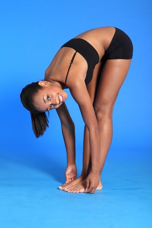 Fitness warm up stretch exercise bending over touching toes by a beautiful young athletic african american fitness woman wearing black sports bra and briefs underwear. photo