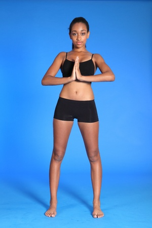 Meditating in standing pose by fit beautiful young athletic african american fitness woman wearing black sports bra and briefs underwear. photo