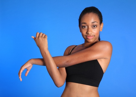 Shoulder stretch warm up exercise by fit beautiful young athletic african american fitness woman wearing black sports bra. photo