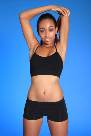 Shoulder stretch warm up exercise by beautiful young athletic african american fitness woman wearing black sports bra and briefs underwear showing off fit, healthy body. photo