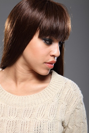 Headshot of beautiful young mixed race model woman in stunning profile, with long brown hair taken against grey backdrop. Stock Photo - 11148821