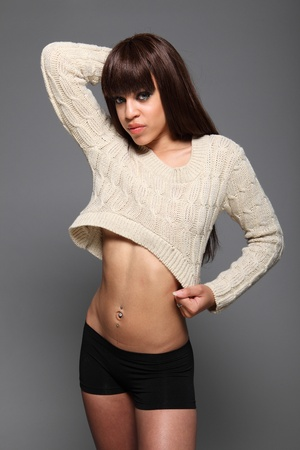 Belly button piercings on sexy young mixed race fashion model woman with beautiful smokey eye make up showing flat stomach and long brown hair, wearing short knitted top and black boy shorts. photo