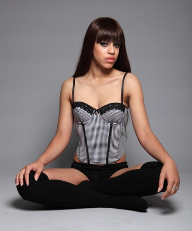 long legged: Sitting cross legged on floor a beautiful sexy young mixed race glamour model woman with long brown hair, wearing black and white bustier style lingerie. Stock Photo