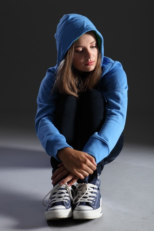 distressed: Hoodie on for distressed and frightened young blonde teenager girl sitting on floor looking scared and alone with big sad eyes, wearing jeans and blue jumper.