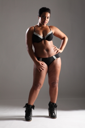 BBW big beautiful african american woman showing off plus size curvy figure wearing sexy black lingerie and boots. photo