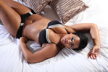 bra model: Glamour model BBW big beautiful african american woman showing off large cleavage and voluptuous plus size curvy figure wearing sexy black lingerie lying in bed. Stock Photo