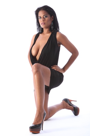 Young beautiful african american fashion model striking sexy pose kneeling on floor wearing short black dress and stiletto heels, showing off big boobs and cleavage. Stock Photo - 11148827