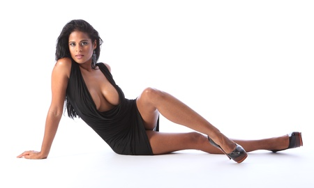 Beautiful breasts: Sitting on floor a young beautiful african american fashion model wearing short black dress and stiletto heels, showing off long legs big boobs and cleavage.