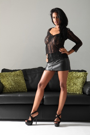 provocative woman: Young beautiful mixed race fashion model wearing short sexy black skirt and lace top with stiletto heels, showing off long legs.