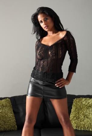 minijupe: Belle jeune mod�le mixte de mode de course portant courte jupe sexy en noir et top en dentelle posant � c�t� canap� en cuir avec des coussins verts.