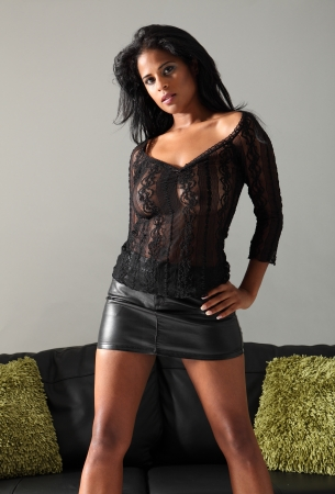 Young beautiful mixed race fashion model wearing short sexy black skirt and lace top posing next to leather sofa with green cushions. photo