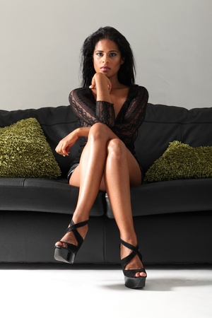 mini skirt: Young beautiful mixed race fashion model with long legs and stilettos wearing short sexy black skirt and lace top sitting cross legged on leather sofa with green cushions.