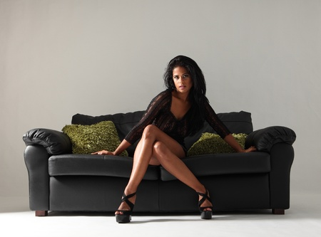 Young beautiful mixed race fashion model with long legs and stilettos wearing short sexy black skirt and lace top sitting cross legged on leather sofa with green cushions. photo