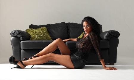 mini falda: Joven y bella modelo de moda mestiza con las piernas largas y tacones de aguja usar minifalda sexy negro y de encaje arriba sentado en el suelo junto al sofá de cuero con cojines verdes.