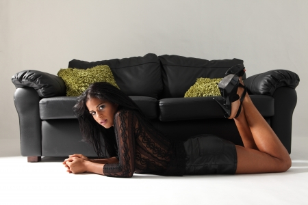 Young beautiful mixed race fashion model with long legs and stilettos wearing short sexy black skirt and lace top lying on floor next to leather sofa with green cushions. photo
