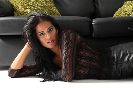 long black hair: Young beautiful african american fashion model wearing black lace top lying on floor in front of leather sofa with green cushions.