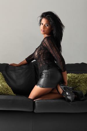 mini jupe: Belle jeune modèle de la mode africaine américaine portant top en dentelle noire, cuir mini-jupe et talons à genoux sur un canapé en cuir noir avec des coussins verts.