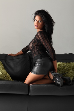 mini falda: Hermosa joven modelo africano de la moda americana llevaba la parte superior de encaje negro, de cuero mini-falda y tacones de rodillas para arriba en un sofá de cuero negro con cojines verdes.