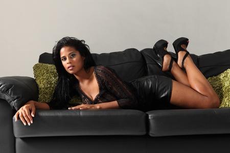 minifalda: Sexy curvas joven modelo africano de la moda americana llevaba la parte superior de encaje negro, mini falda y tacones altos que yacen en el sofá de cuero con cojines verdes.