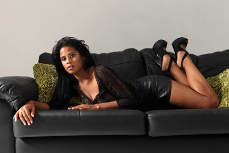 Sexy curvy young african american fashion model wearing black lace top, mini-skirt and high heels lying on leather couch with green cushions. photo