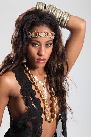 Beautiful young amazon woman of mixed race ethnicity, wearing black lingerie and gold accessories. Woman has long brown hair and striking sexy pose. photo