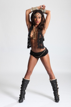 Beautiful young amazon woman of mixed race ethnicity, wearing black lingerie and gold accessories. Woman has long brown hair and striking sexy pose with arms raised. photo