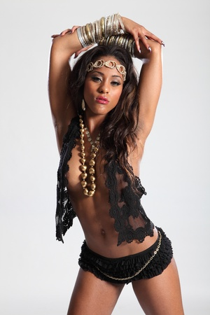 Sexy cleavage on beautiful young amazon woman of mixed race ethnicity, wearing black lingerie and gold accessories. Woman has long brown hair and arms raised over her head. photo