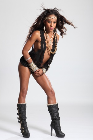 Sexy in boots a beautiful young amazon woman of mixed race ethnicity, with long brown hair wearing black lingerie and gold accessories. photo