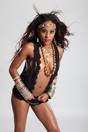boobs: Sexy boobs and cleavage of beautiful young amazon woman of mixed race ethnicity, with long brown hair wearing black lingerie and gold accessories.