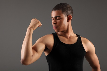 Showing off his bicep muscles a handsome young african american sportsman wearing black vest, shot against grey background. photo